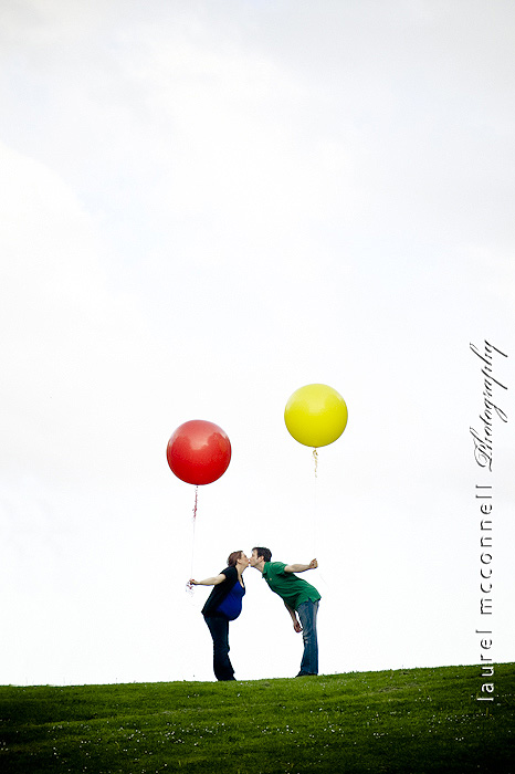 pregnant woman and her man with some big yellow and red balloons on the top of a hill