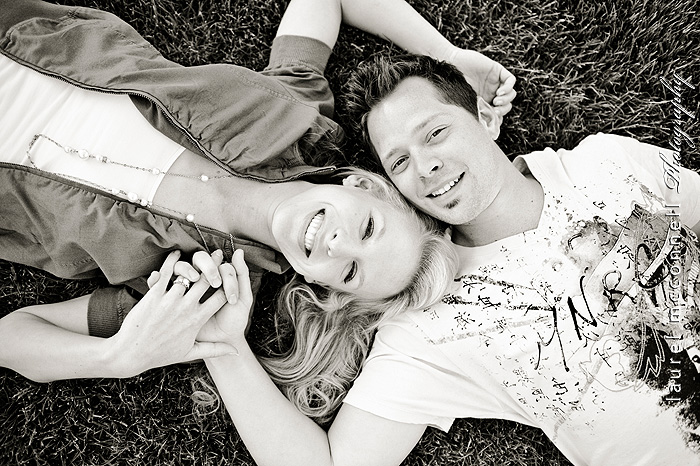a black and white image of an engaged couple lying in the grass