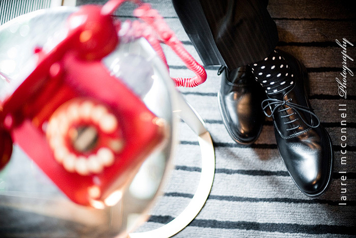 seattle wedding photographer Laurel McConnell's photo of a red vintage phone and stylish polka dot socks on groom