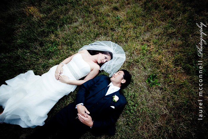 bride and groom relaxing on the grass by Laurel McConnell