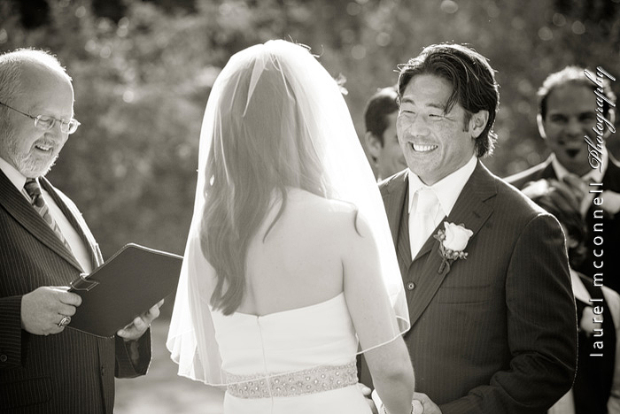 groom smiling at bride during their seattle wedding ceremony by  photographer laurel mcconnell