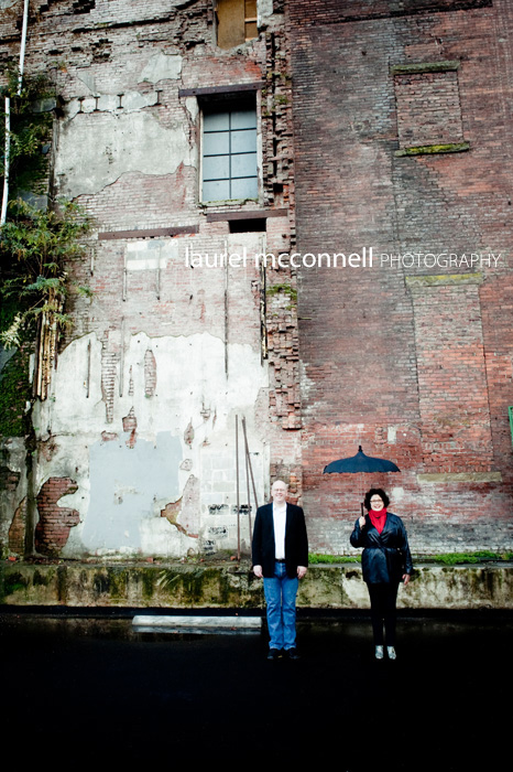 couple by an old brick wall with a vintage black umbrella