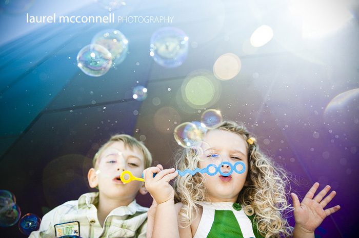 two children blow bubbles in the sun at the Seattle Center EMP museum