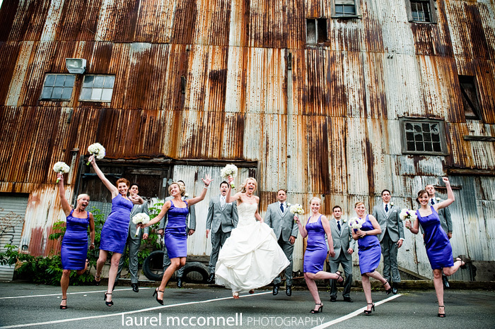 wedding party in purple and grey jumping in front of a rusty  warehouse