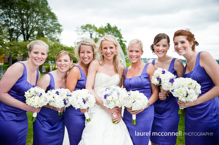 smiling stylish bridesmaids in purple satin dresses with bride and bouquets