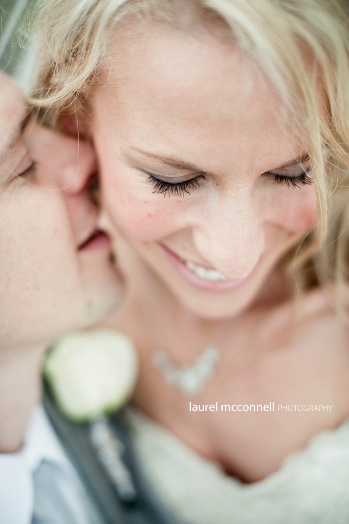 groom whispering secret to bride with thick eyelashes
