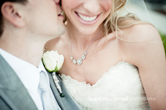 groom snuggling bride with beautiful diamond bridal jewelry