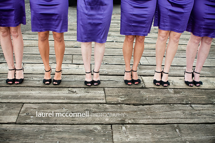 purple bridesmaid dresses and black shoes on dock
