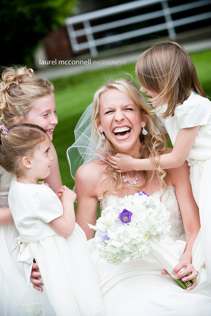 bride laughing with flower girls