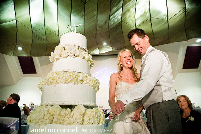 bride and groom cutting cake under a parachute