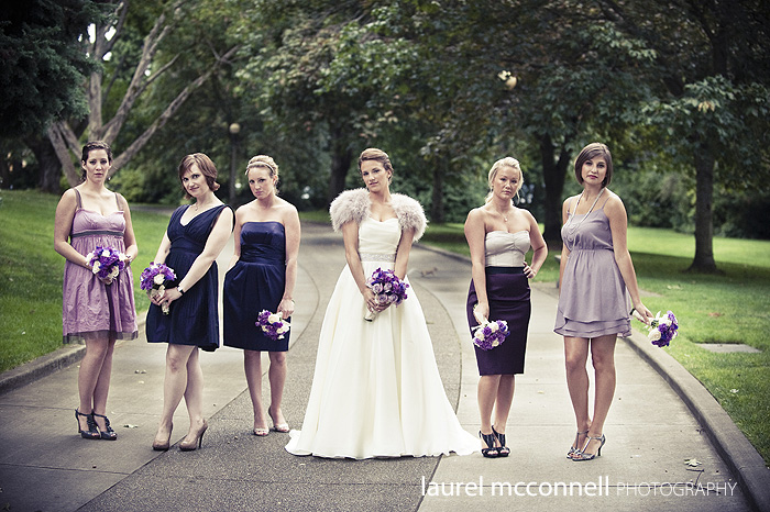 bridesmaids with their pretty faces on, in the park, with purple dresses and feathers.