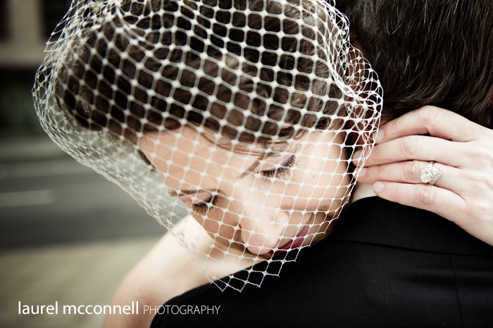 bride hugging groom with a birdcage veil