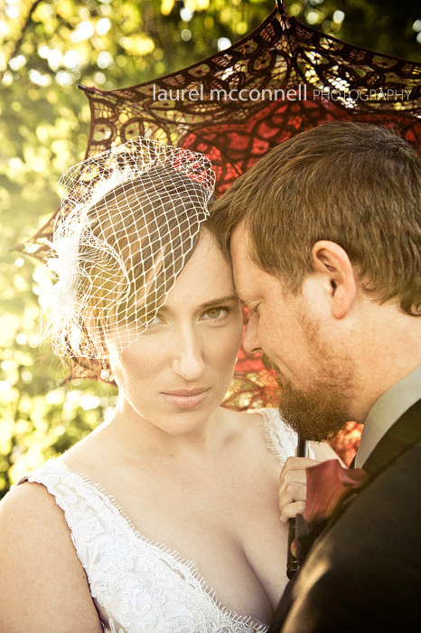beautiful evening light on a bride with birdcage veil and parasol and groom