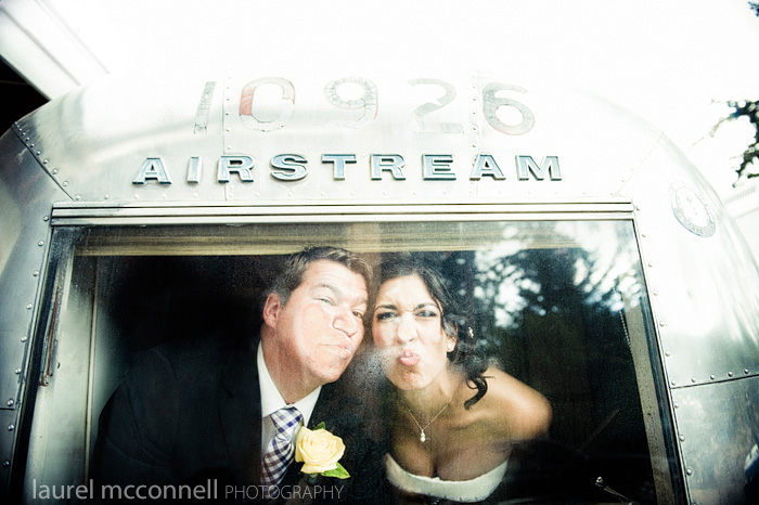 a bride and groom smooshing their faces against the window of their Airstream trailer