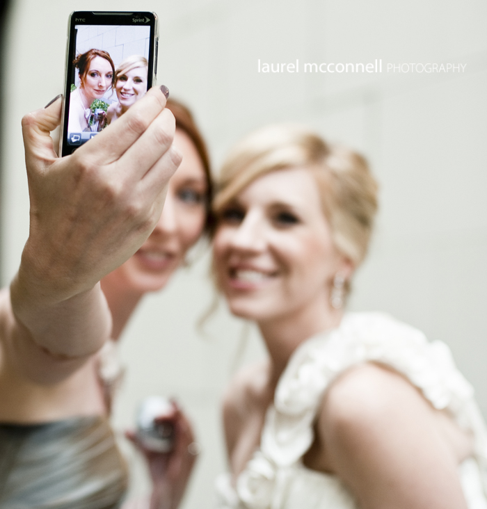 bride and maid of honor taking a self portrait with her iphone