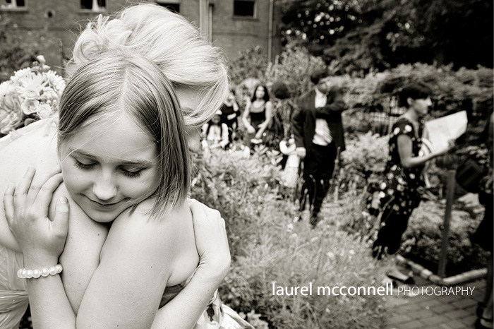 bride hugging her daughter during family portraits at her wedding