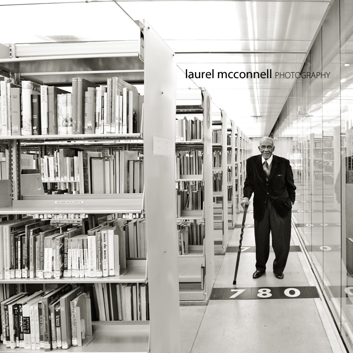 a black and white portrait of philanthropist and avid reader Samuel McKinney in the stacks at Seattle Public Library