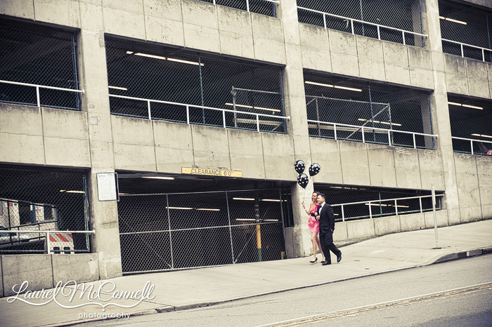 a fancy couple walking by an urban parking garage downtown with balloons for engagement pictures