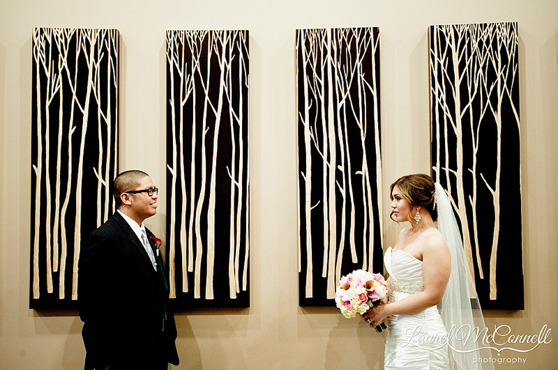 bride and groom's portrait by tribal art of trees at the tulalip casino on a rainy day