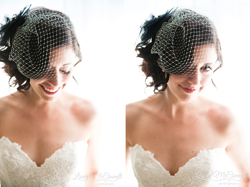 beaming bride with sideswept hair and birdcage veil in front of window laughing