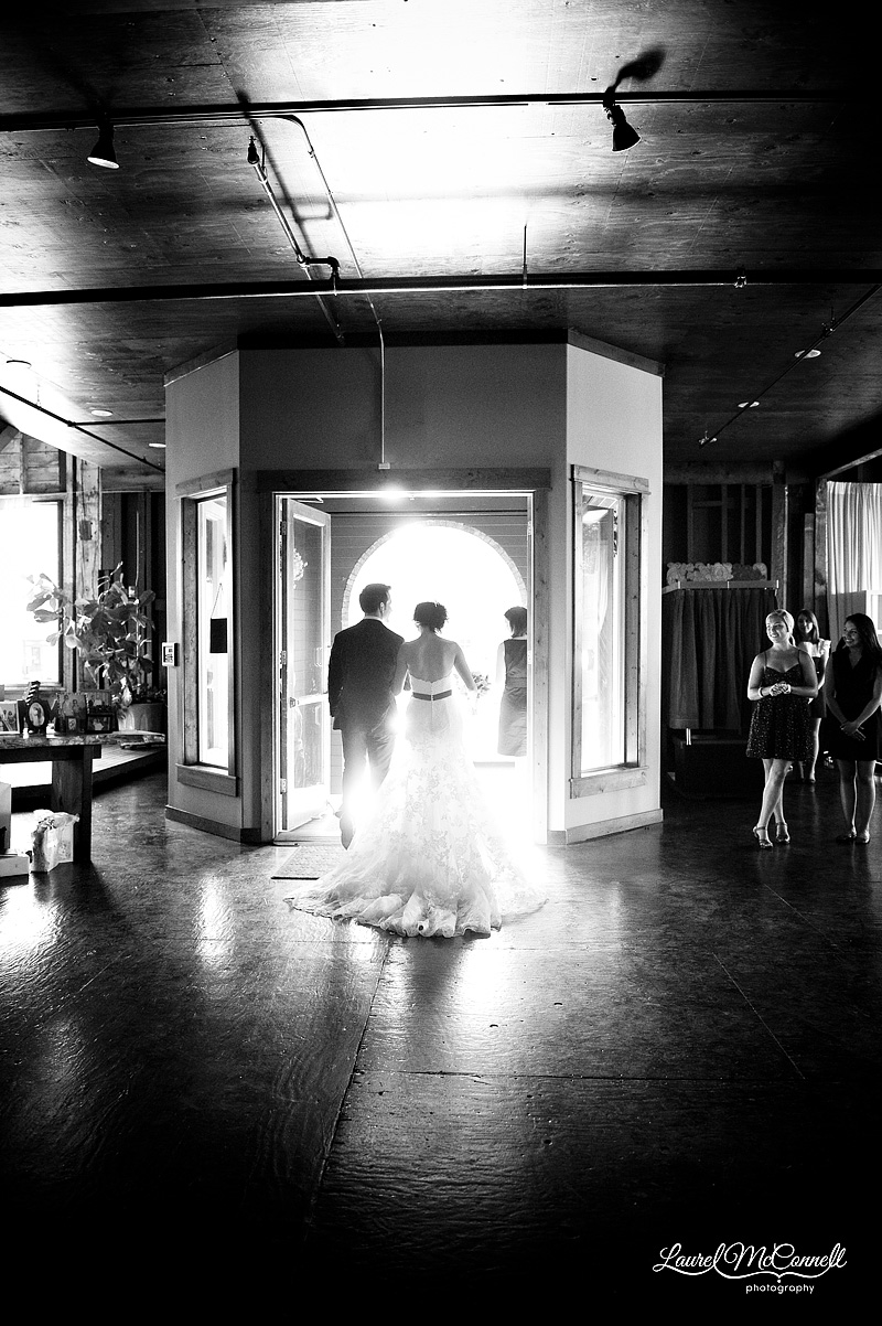 bride and groom silhouetted as they're walking down the aisle in black and white