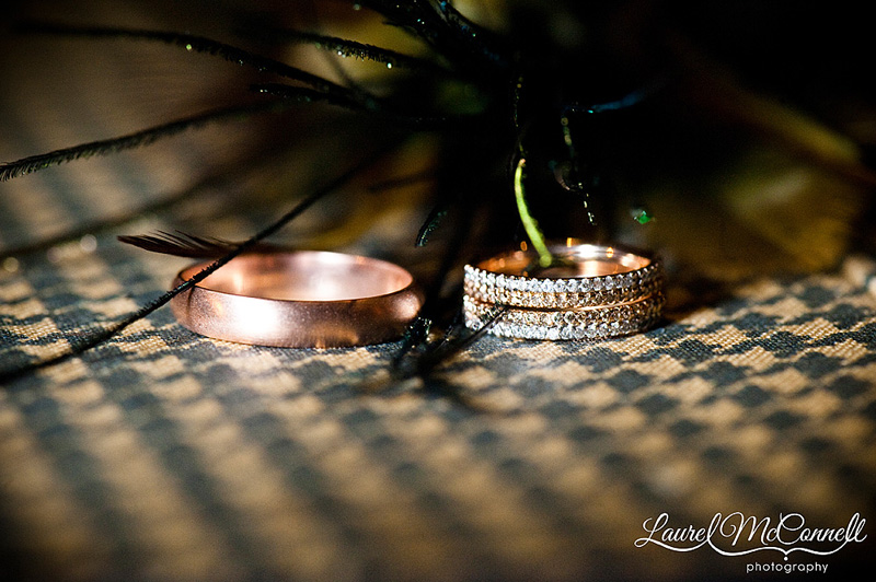rose gold wedding bands (a cool ring shot) on vintage suitcase with peacock feathers