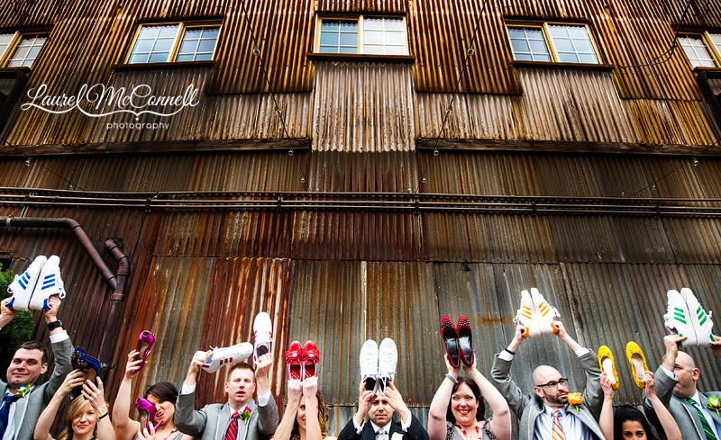 fun wedding party photo at georgetown ballroom where the bridesmaids and groomsmen are holding up their adidas wedding shoes. photographed by seattle wedding photographer laurel mcconnell