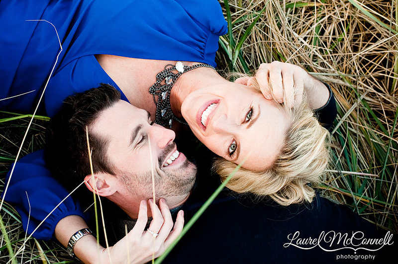 couple laying in beach grass for engagement photos in seattle, washington