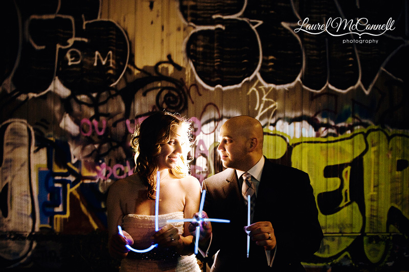 nighttime wedding portraits in front of an urban graffiti wall. the bride and groom are holding glowsticks made to look like their wedding logo. photographed by seattle wedding photographer laurel mcconnell