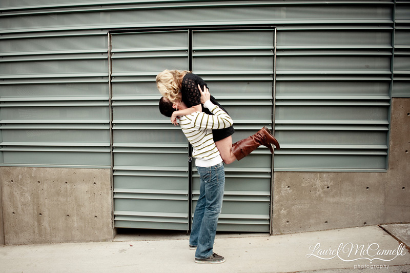 groom picking up his bride during an urban engagement portrait session in seattle
