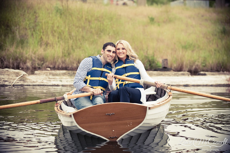 couple in a wooden row boat for engagement photos