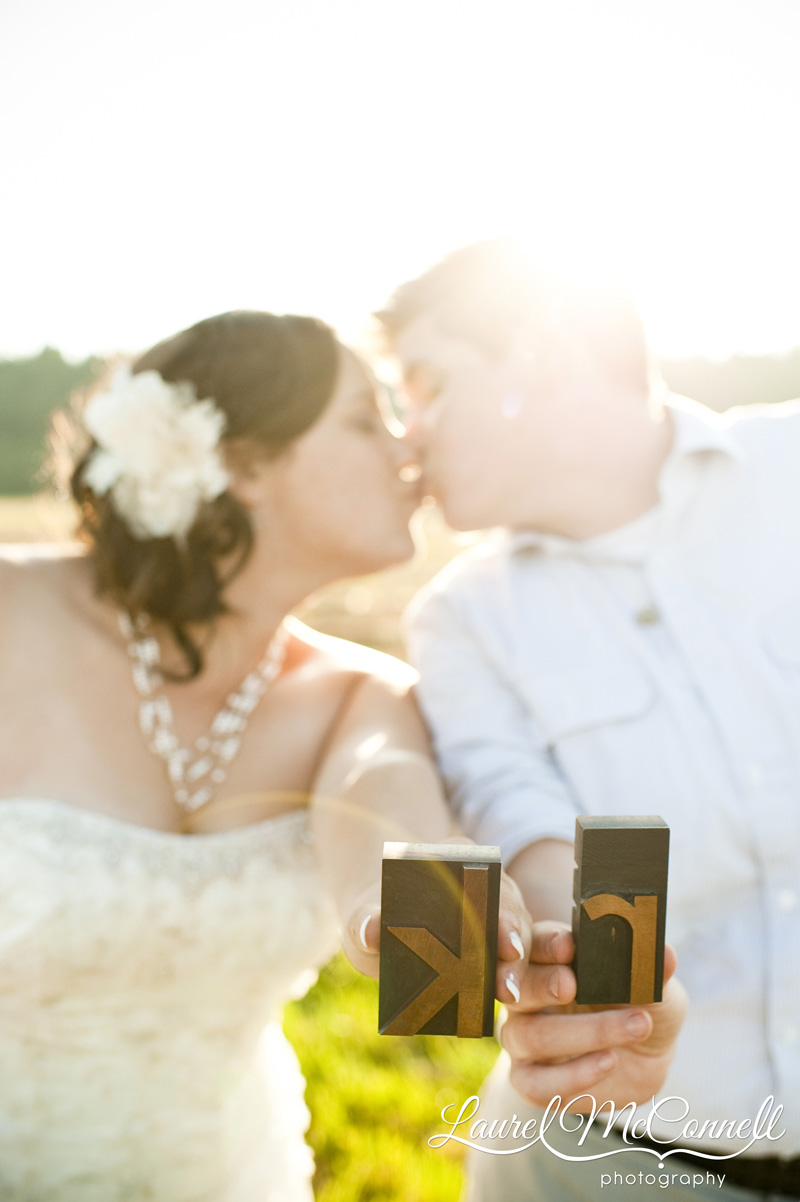 Sunlit brides kissing with letterpress decorations.