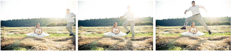 Smiling bride sits in a field of grass while her wife runs and jumps over her.