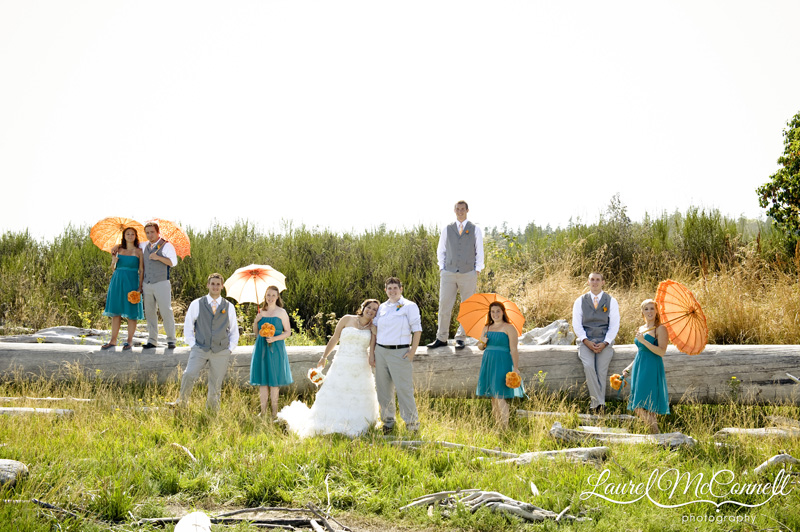 Orange and turquoise wedding party with parasols.