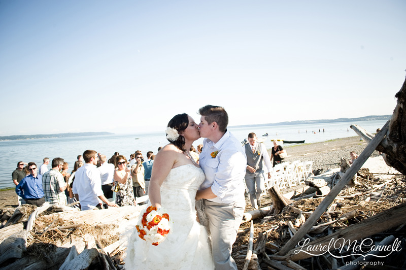 Brides kiss as new wives amongst driftwood.