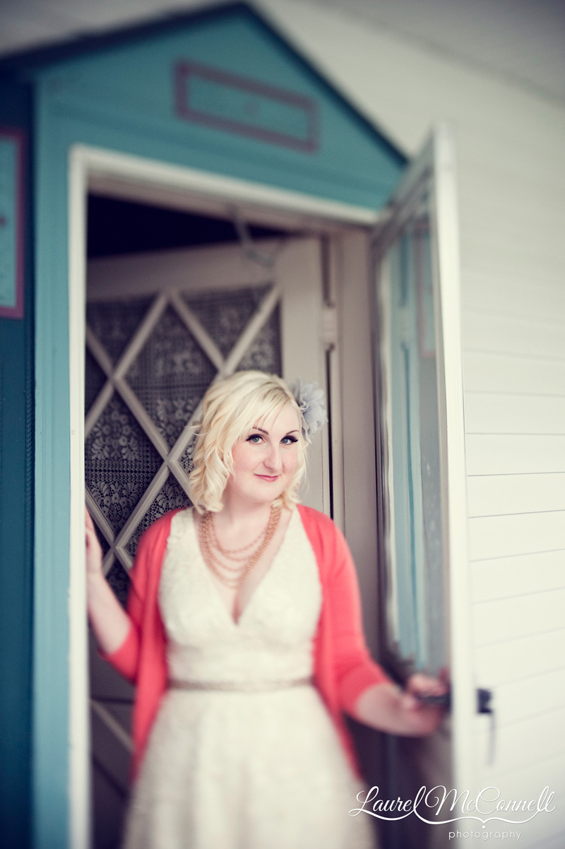 blonde bride with coral sweater in a turquoise doorway wearing a short wedding dress