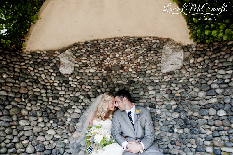 sweet bride and groom snuggling on a rock bench at Roche Harbor