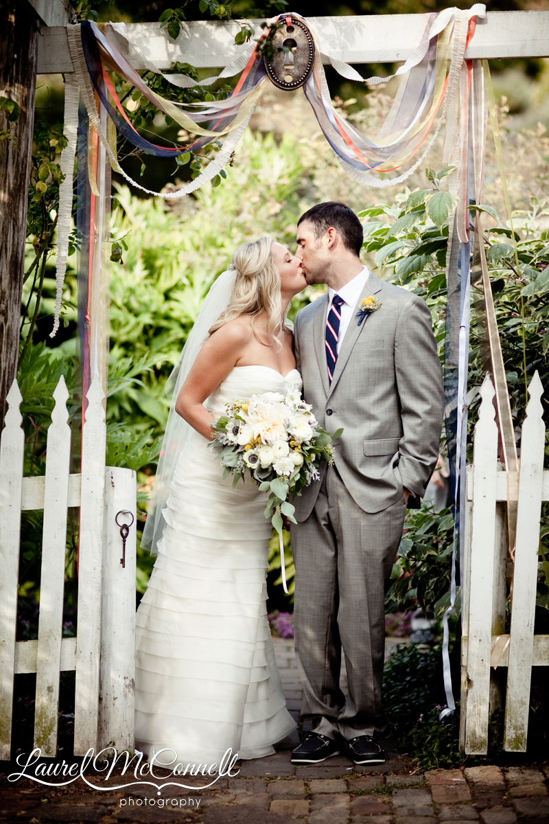 newlywed bride and groom kiss under a ribbon arch with a lock at the entrance to their ceremony