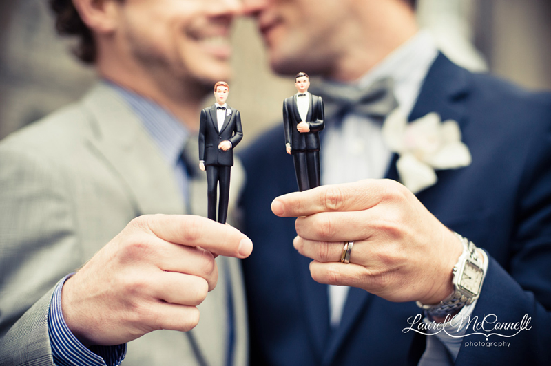 Creative marriage equality wedding portrait of grooms with cake toppers by Seattle photographer Laurel McConnell.
