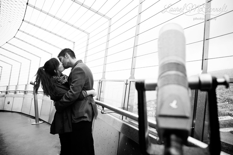 a sweet portrait of the newly engaged couple on the seattle center observation deck, next to a telescope