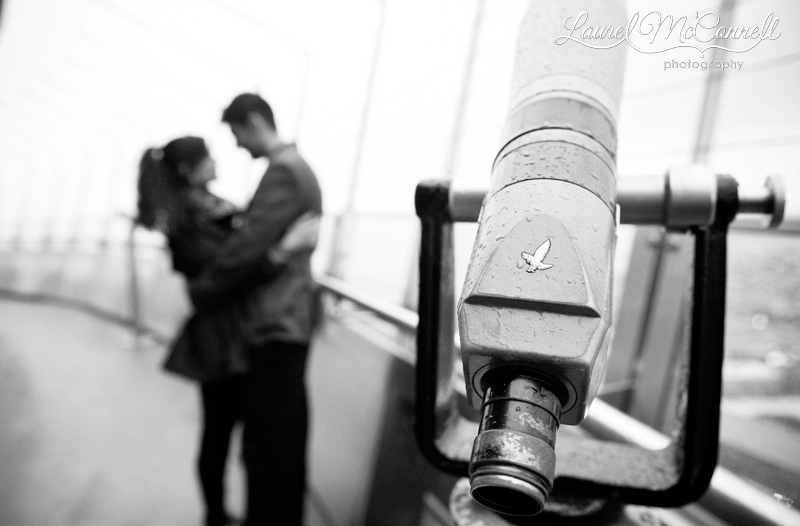 selective focus of a couple on the space needle deck