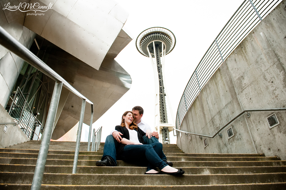 pausing for a picture on the stairs at the emp with the space needle behind during engagement photos