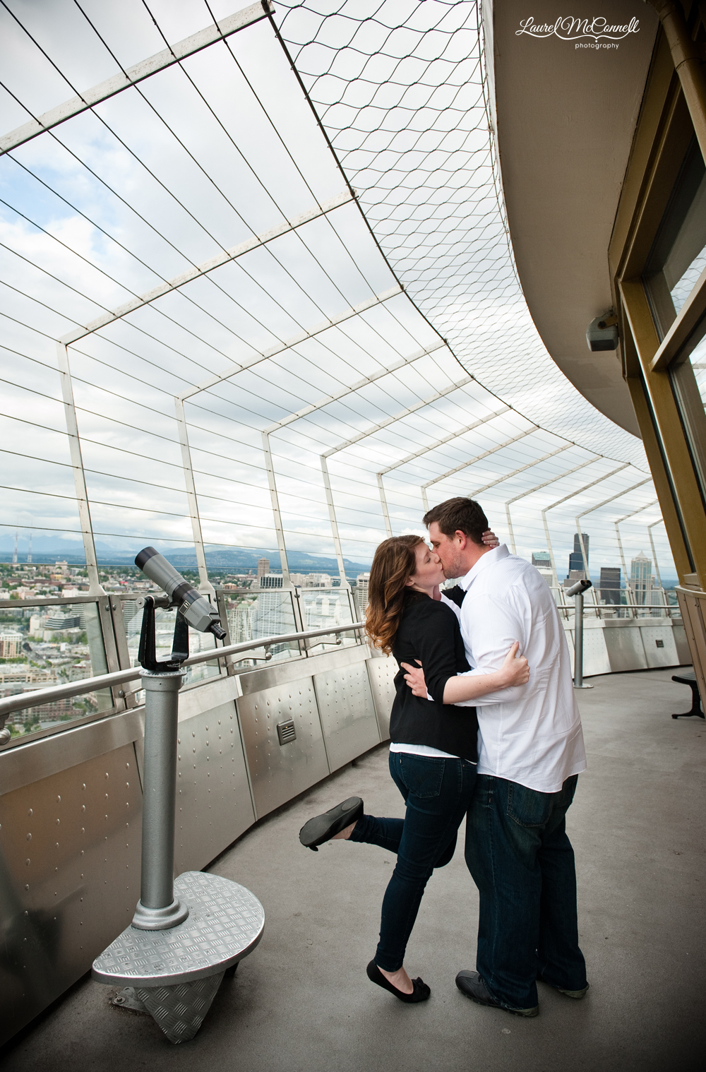a dramatic kiss overlooks the seattle skyline atop the space needle after he proposed
