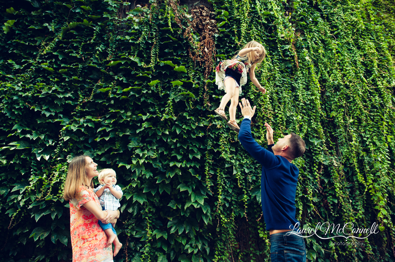 Seattle family playing in front of an ivy wall photographed by Laurel McConnell Photography.