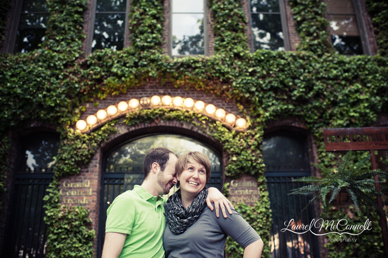 Couple laughs together in front of Seattle's Grand Central Arcade during fun engagement session with Laurel McConnell Photography.