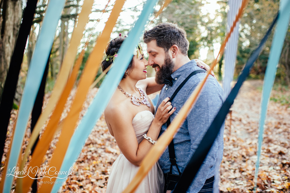 couple cuddling behind a curtain of teal and gold ribbons in the woods