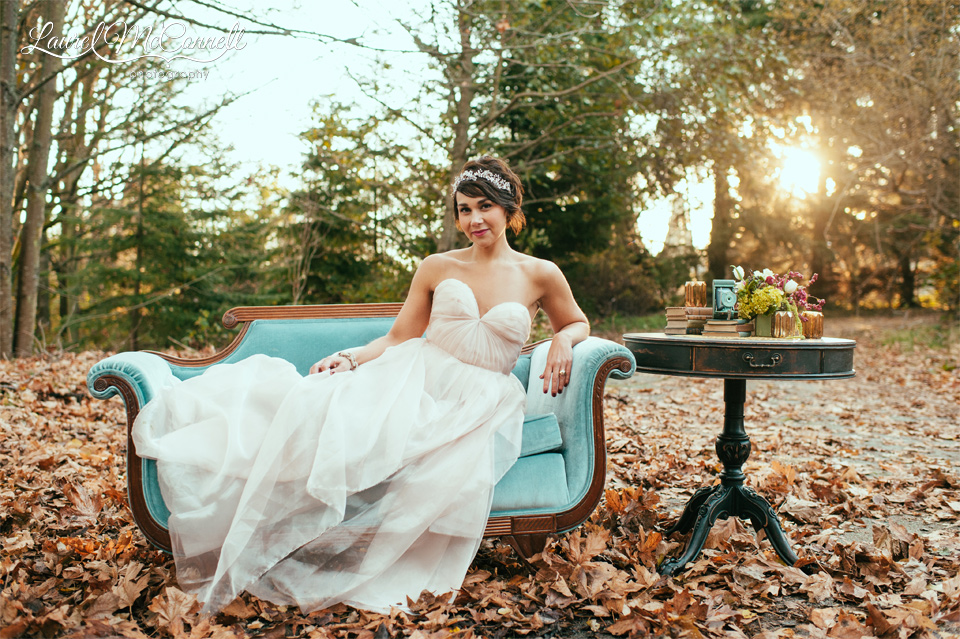bride with blush gown on a vintage turqoise couch in the woods