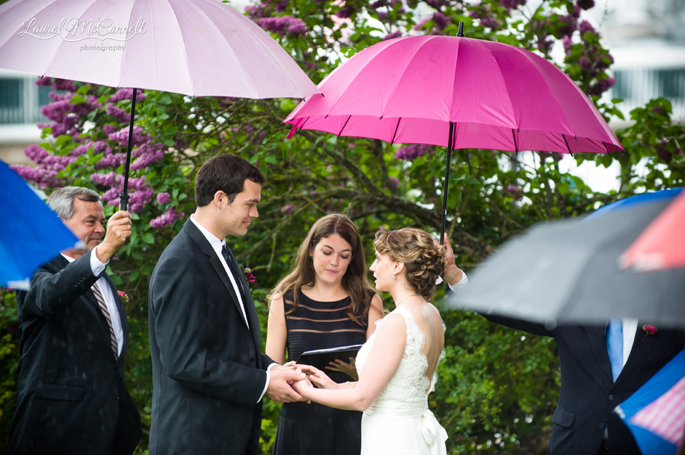 Couple says vows under umbrellas.