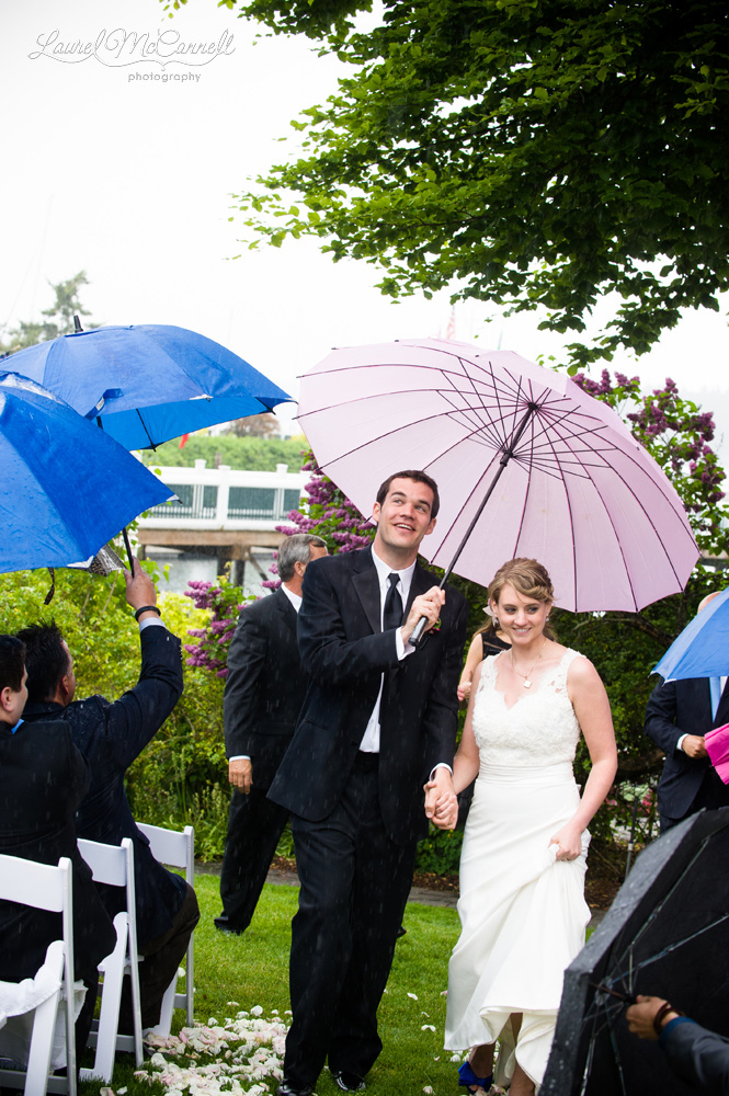 Couple comes down the aisle under an umbrella.