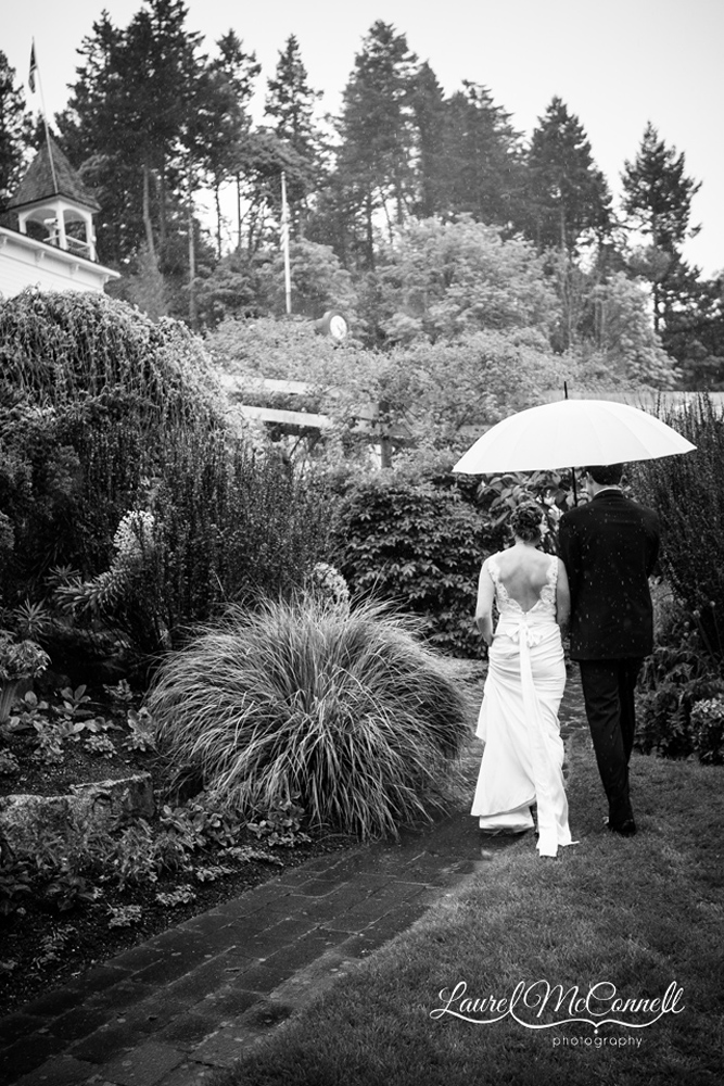 Bride and groom exit ceremony under umbrella.